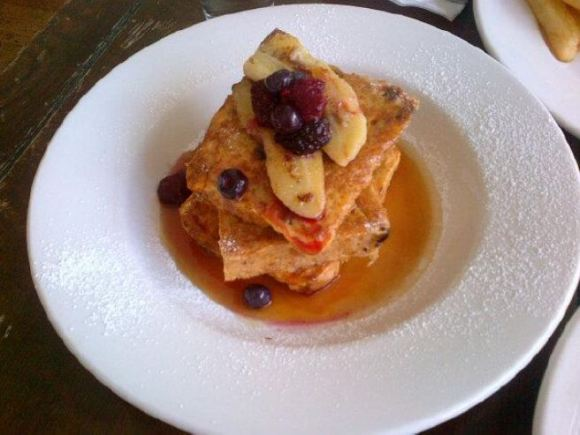 Delicious stack of Gluten Free French Toast, with banana, berries and maple syrup. MMMM!